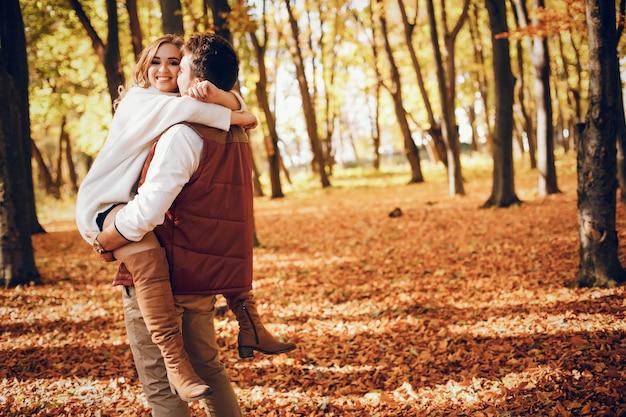 Coppia elegante in un parco soleggiato autunno Foto Gratuite