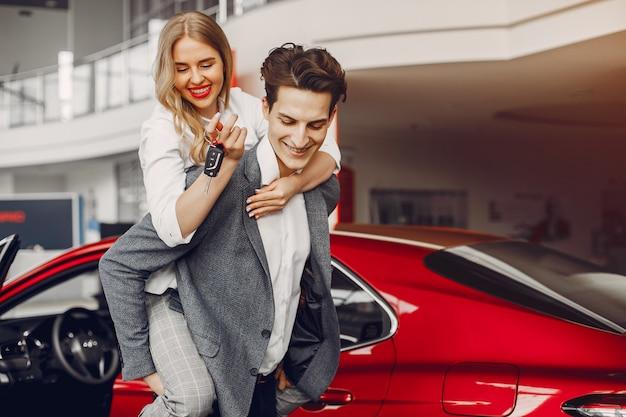 Coppia elegante in un salone di auto Foto Gratuite