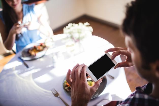 Coppia facendo clic sulla foto di un alimento sul piatto Foto Premium
