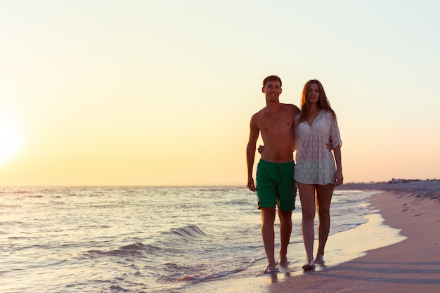 Coppia fare una passeggiata sulla spiaggia Foto Premium