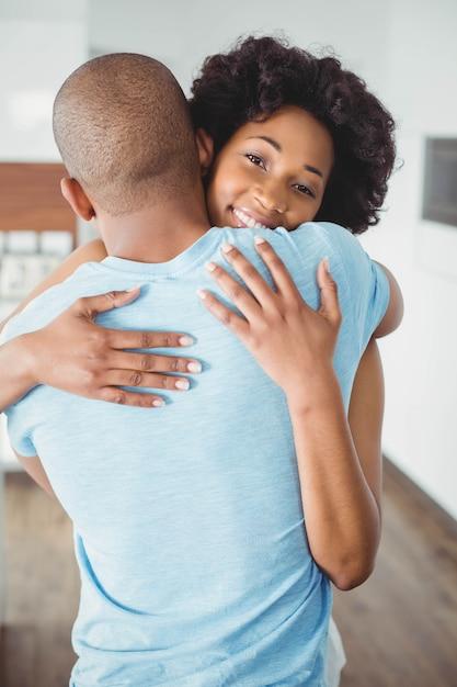 Coppia felice abbracciando in cucina Foto Premium