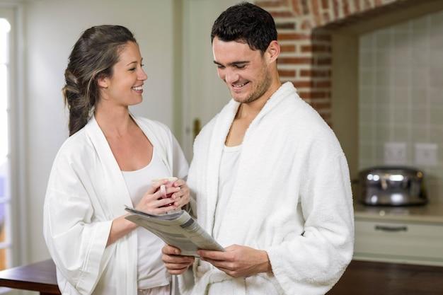 Coppia felice in accappatoio, leggendo il giornale in cucina Foto Premium