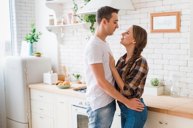 Coppia felice in amore insieme abbracciando in cucina Foto Gratuite