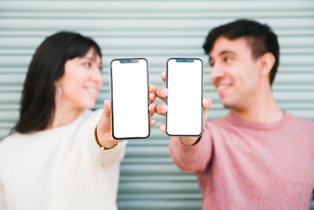 Coppia felice in piedi con gli smartphone Foto Gratuite
