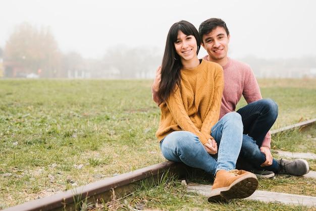 Coppia felice seduto su rotaie e coccole Foto Gratuite