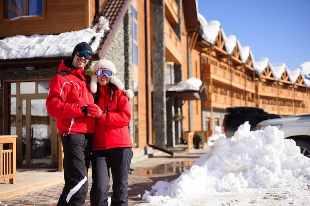Coppia godendo la vista di cottage e chalet in una stazione sciistica Foto Premium