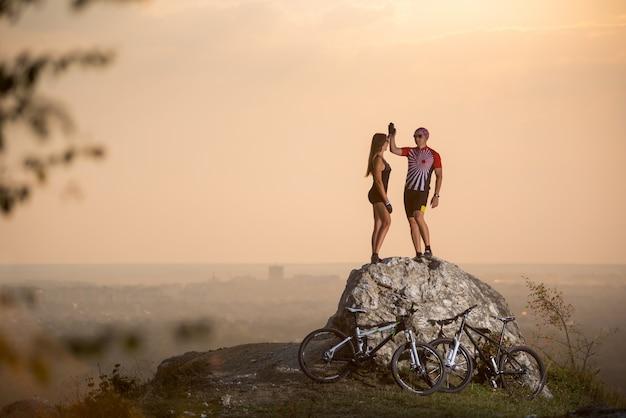 Coppia i motociclisti che stanno su una roccia e che danno il livello cinque alla sera dell'estate con fondo vago. Foto Premium