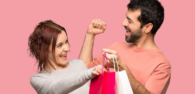 Coppia i sacchetti della spesa della tenuta nella posizione di vittoria sopra fondo rosa isolato Foto Premium
