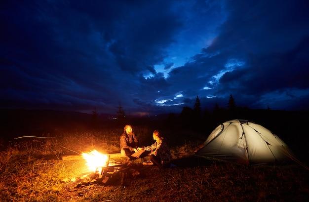 Coppia i turisti che hanno un riposo durante la notte in campeggio Foto Premium