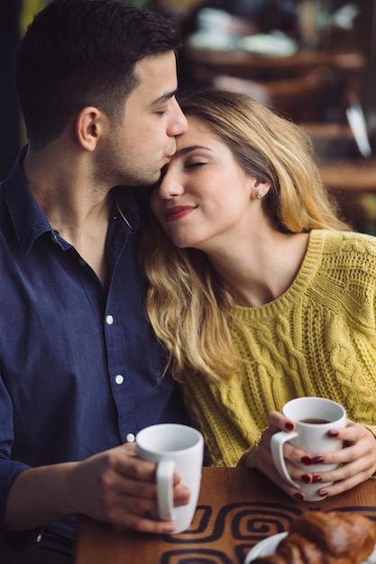 Coppia in amore, bere il caffè nella caffetteria Foto Gratuite