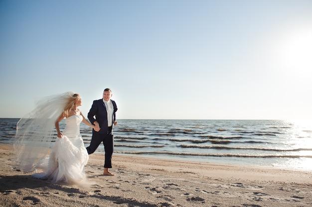 Coppia in amore sulla spiaggia il giorno delle nozze. Foto Premium