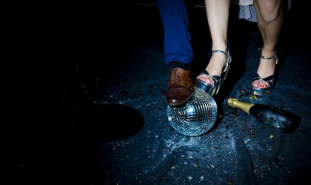 Coppia in piedi sul pavimento con palla da discoteca Foto Gratuite