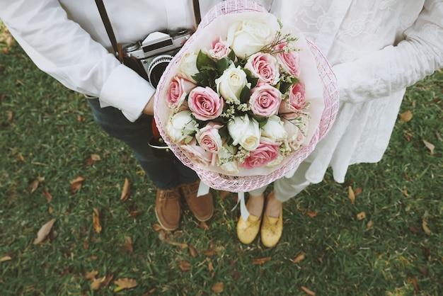 Coppia in possesso di un bouquet di nozze Foto Gratuite