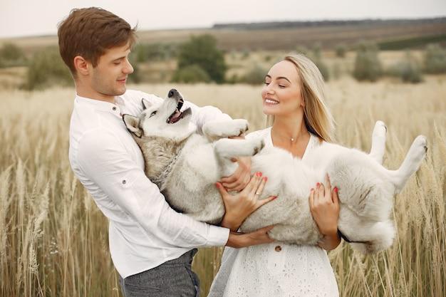 Coppia in un campo autunnale a giocare con un cane Foto Gratuite