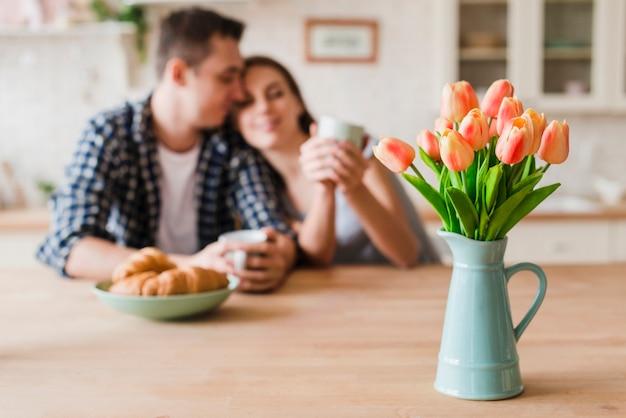 Coppia innamorata accoccolato a tavola e godendo il tè Foto Gratuite