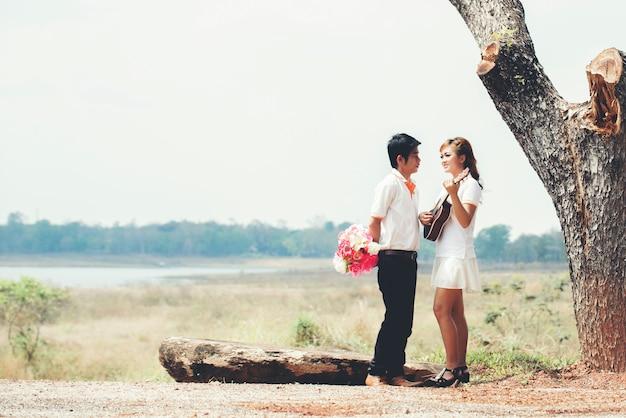 Coppia innamorata di suonare la chitarra in natura Foto Gratuite