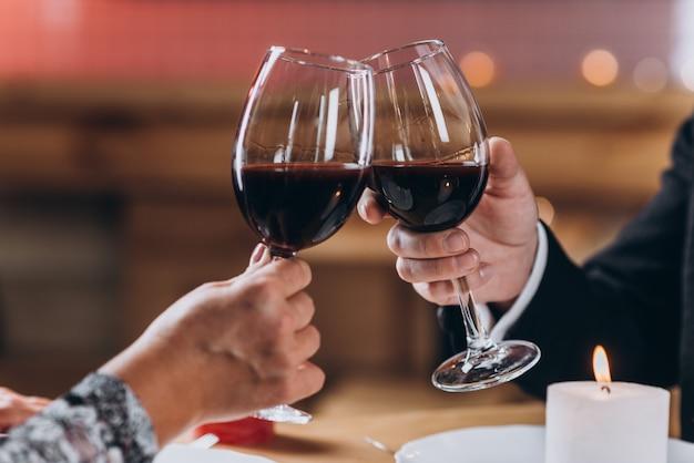 Coppia innamorata solleva bicchieri di vino rosso Foto Premium