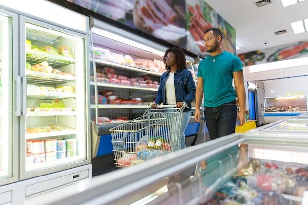 Coppia interrazziale di clienti che acquistano cibo insieme Foto Gratuite