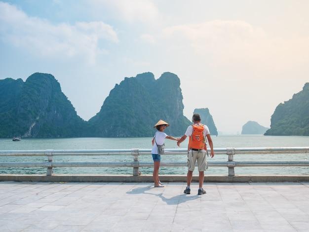 Coppia la camminata congiuntamente sulla passeggiata alla città di halong, vietnam, vista dei culmini della roccia della baia di ha long nel mare. uomo e donna divertirsi viaggiando insieme in vacanza al famoso punto di riferimento. Foto Premium