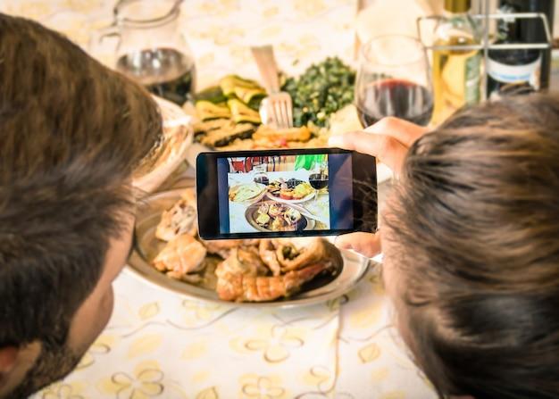 Coppia la presa della foto dell'alimento con lo smart phone mobile al ristorante Foto Premium