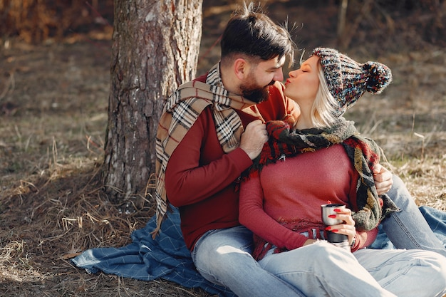 Coppia la seduta da un albero in una foresta della molla Foto Gratuite