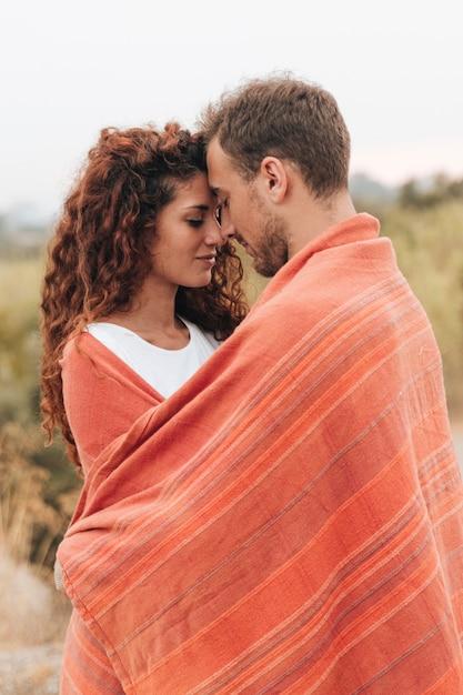 Coppia lateralmente avvolta in una coperta Foto Gratuite