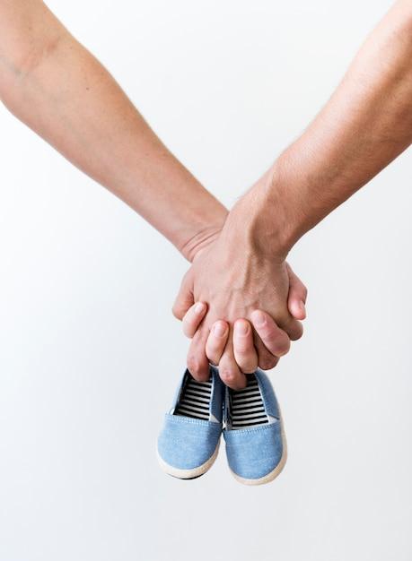 Coppia le mani che tengono le scarpe della ragazza del neonato Foto Premium