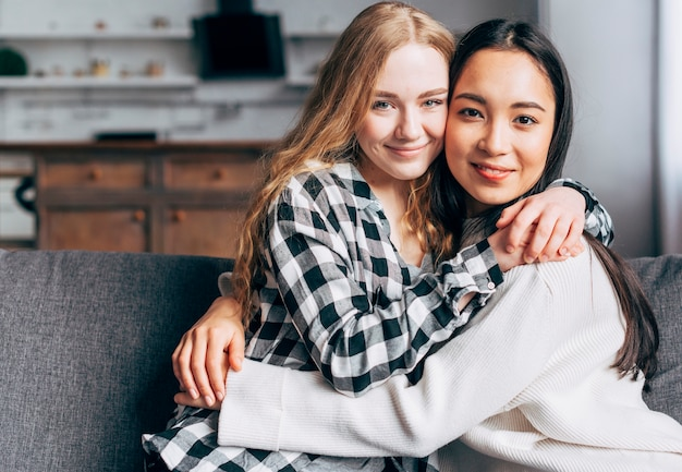 Coppia lesbica abbracciarsi e guardando la fotocamera Foto Gratuite