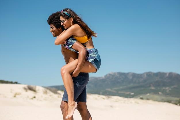 Coppia multirazziale camminando sulla spiaggia Foto Gratuite