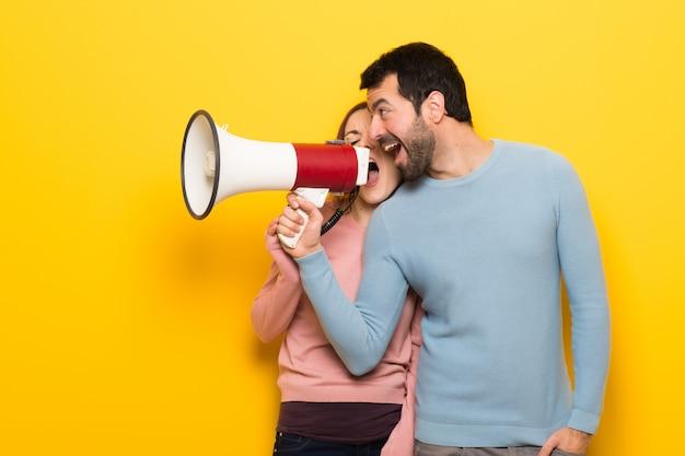 Coppia nel giorno di san valentino urlando attraverso un megafono Foto Premium