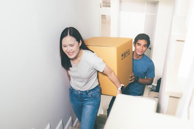 Coppia portando pesanti scatole in movimento insieme. Foto Premium