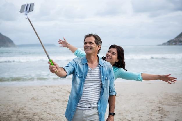 Coppia prendendo selfie sulla spiaggia Foto Premium
