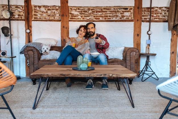 Coppia rilassata a casa sul divano a guardare la tv e mangiare popcorn Foto Premium