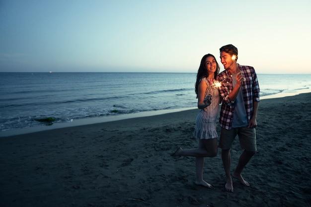 Coppia romantica con sparkler in una spiaggia di tramonto Foto Gratuite