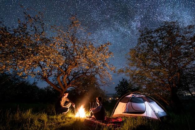 Coppia romantica escursionisti seduti a un falò vicino alla tenda sotto gli alberi e il bel cielo notturno pieno di stelle e via lattea Foto Premium