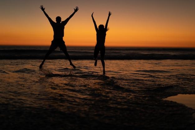 Coppia saltando insieme con le braccia in alto sulla spiaggia Foto Gratuite
