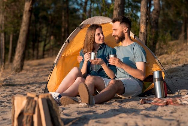 Coppia seduta accanto alla tenda e bevendo Foto Gratuite