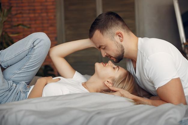 Coppia seduta su un letto in una stanza Foto Gratuite