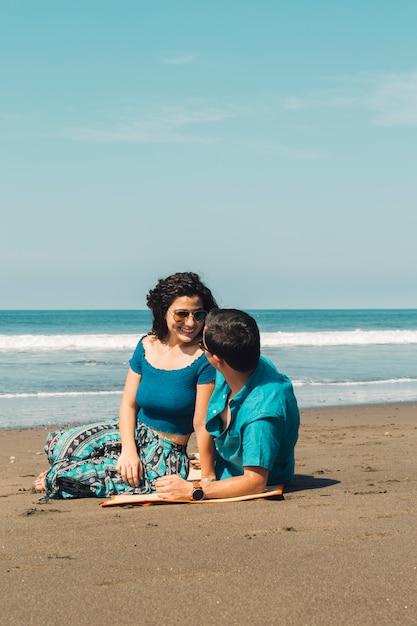 Coppia seduta sulla spiaggia e guardando a vicenda Foto Gratuite