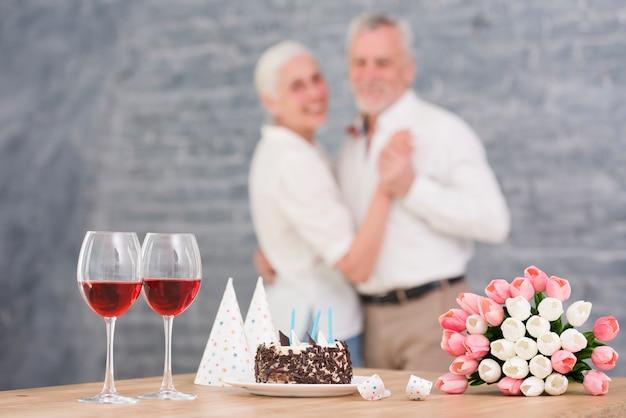 Coppia sfocato che balla davanti al bicchiere di vino; torta deliziosa; fiori di tulipano sul tavolo di legno Foto Gratuite