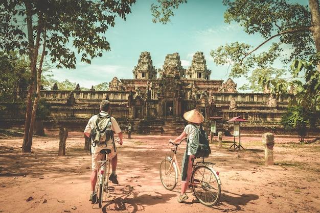 Coppia turistica in bicicletta intorno al tempio di angkor Foto Premium