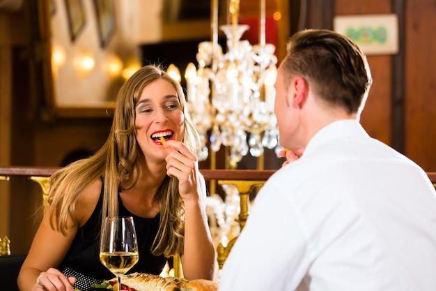 Coppia, uomo e donna un raffinato ristorante mangiano fast food e patatine fritte Foto Premium