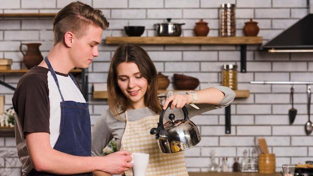 Coppia versando il tè in cucina Foto Gratuite