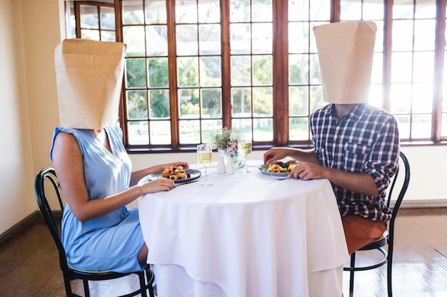 Coppia volti coperti con un sacco di carta nel ristorante Foto Premium