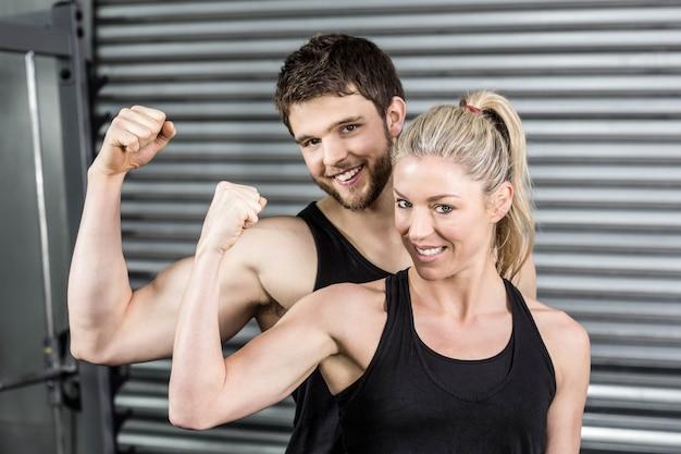Coppie adatte che mostrano le armi muscolari alla palestra del crossfit Foto Premium