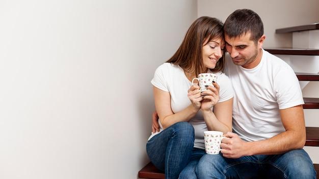 Coppie adorabili che bevono caffè e che si siedono sulle scale Foto Gratuite