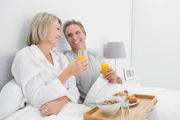 Coppie allegre che mangiano succo d'arancia a colazione a letto Foto Premium
