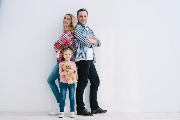 Coppie allegre con la loro figlia che posa nella parete bianca anteriore Foto Gratuite