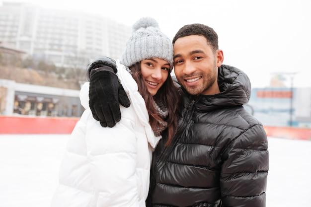 Coppie amorose attraenti che pattinano alla pista di pattinaggio sul ghiaccio all'aperto. Foto Gratuite