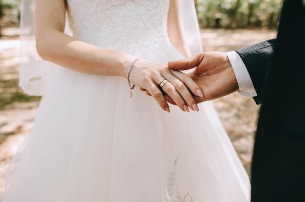 Coppie amorose che si tengono per mano con gli anelli contro il vestito da sposa Foto Premium